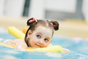 Little girl swimming with a yellow n