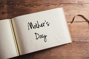Mothers day sign. Photo album. Studio shot, wooden, background.