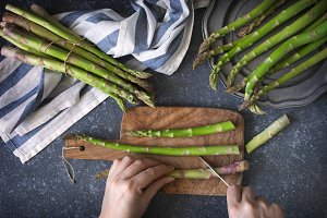 Female hands cut raw asparagus