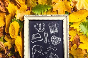 Oktoberfest symbols in picture frame, chalk drawings, autumn lea