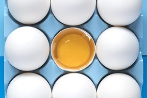 Raw chicken eggs on blue background