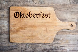 Octoberfest sign on cutting board, copy space, wooden background