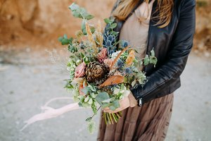 Bride hold a rustic bouquet with succulents, roses and pine cone. Artwork. Country style wedding.