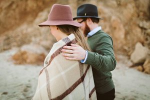 A young stylish couple is having fun walking on the sea coastline. Newlyweeds dressed in hats and plaid. Rear view