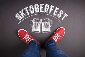 Oktoberfest sign with beer mugs and red sneakers.