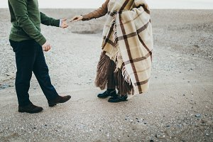 A young stylish couple is having fun walking on the sea coastline. Newlyweeds dressed in casual style clothes and plaid