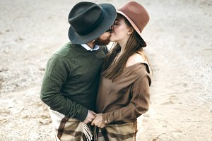 Beautiful Couple of man and woman dressed in country style kissing. Newlyweds in hats. Close-up portrait