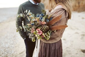 Newlyweds with rustic bouquet in hands stand on seashore. Bride and groom wear in country style clothes and hats.