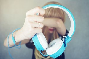 Young woman holding a headphones
