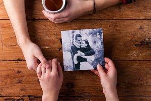 Unrecognizable man holding womans hand. Looking  at their photo.