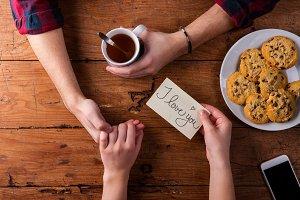 Unrecognizable mans and womans hands. Romantic message. Tea and