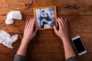 Unrecognizable sad woman holding broken picture of couple in lov