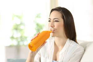 Happy woman drinking orange juice