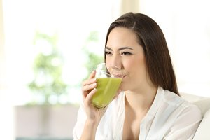 woman drinking a green juice