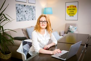 Young woman with long red hair and glasses for view works, prints on a gray laptop keyboard sitting at a wooden table in a bright interior. Subject business, people and technology