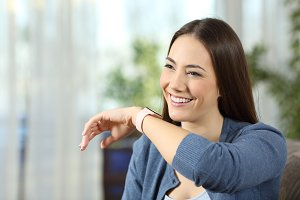 Happy woman talking to a smartwatch