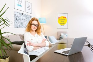 young woman with long red hair in white shirt and glasses for vision works, looks at the camera, uses gray laptop sitting at wooden table in a light interior. Subject business, people and technology