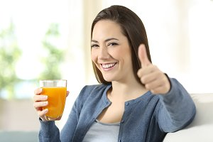 consumer holding an orange juice