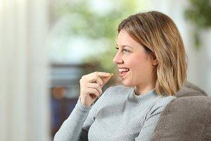 happy woman taking a vitamin pill