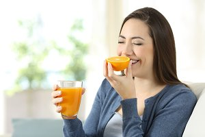 Happy woman smelling an orange