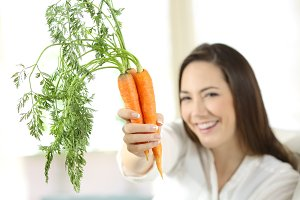 woman showing a bundle of carrots