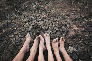 Feet of children on cracked ground