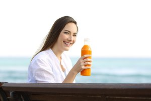 woman holding an orange juice