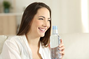 happy woman holding a bottle of wate