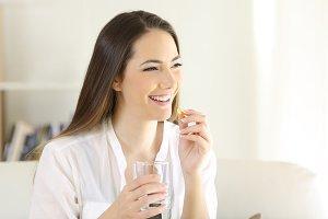 Happy woman taking a vitamin