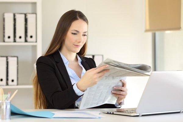 Serious businesswoman reading news