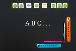 Black art table with stationery supplies with letters A B C on black background