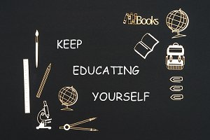 School supplies placed on black background with text keep educating yourself