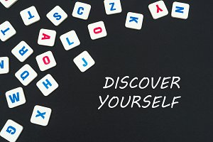 English colored square letters scattered on black background with text discover yourself