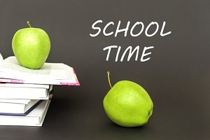 Two green apples and open books with text school time