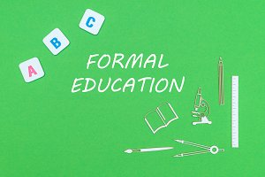 From above wooden minitures school supplies and ABC letters on green background with text formal education