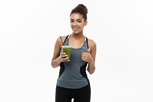 Healthy and Fitness concept - Beautiful American African lady in fitness clothing drinking healthy vegetable drink. Isolated on white background.