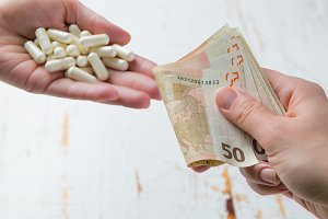 Overpriced drugs concept - hands exchanging money for drugs. Medicine or insurance related crime concept
