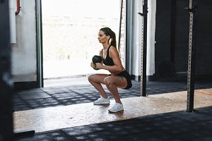 Woman doing squats with kettlebell