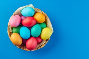 Basket of colorful easter eggs  on blue background