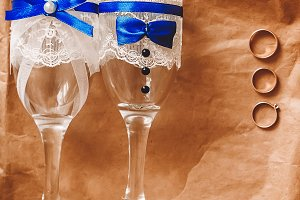 two glasses decorated for wedding ribbons white and blue. lace. bows. gold rings for the bride and groom