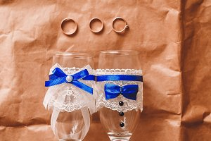 three gold rings. two rings for the bride and one for the groom. glasses decorated with ribbons and lace. blue and white color