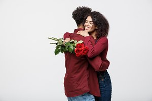 Couple Concept - Young african american couple huging each other and holding romantic red rose.