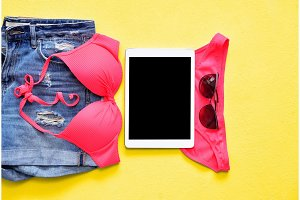 Female summer bikini swimsuit and accessories on blue with tablet and sunglasses.