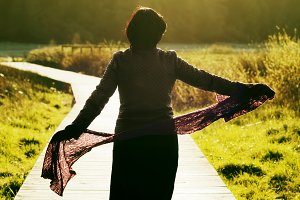 woman with scarf on footpath