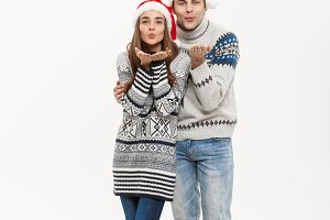 Christmas concept - Full-length Young attractive caucasian couple giving a kiss celebrating for Christmas day.