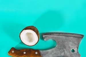 one cut coconut and a sharp ax on a
