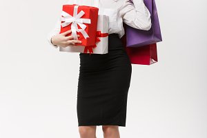 Christmas Concept - beautiful business woman holding shopping bags and present with exhausted feeling.