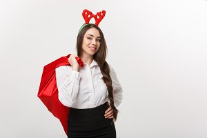Christmas Concept - Young beautiful business woman in christmas theme holding santa red bag.