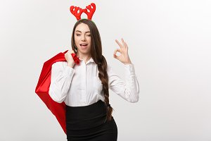 Christmas Concept - Young beautiful business woman in christmas theme holding santa red bag giving ok sign.