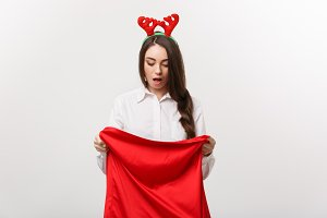 Christmas Concept - Young beautiful business woman surprise with present in santa bag.